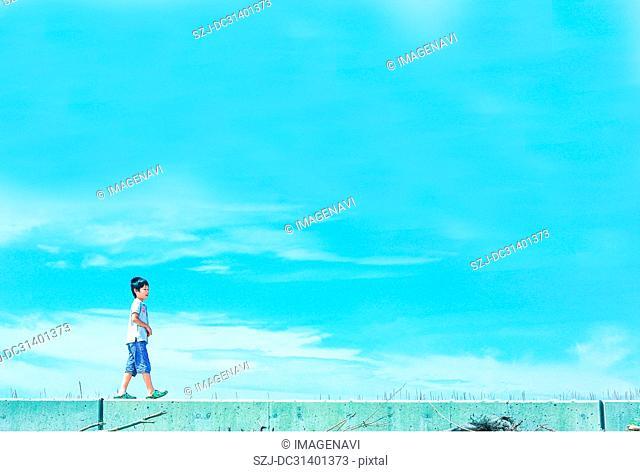 Kid walking on embankment