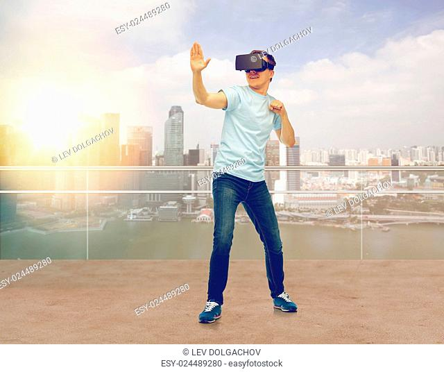 3d technology, virtual reality, entertainment, cyberspace and people concept - young man with virtual reality headset or 3d glasses playing game and fighting...