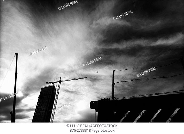 Building under construction and airplane flying in cloudy sky. Lots Rd., Chelsea, London, England
