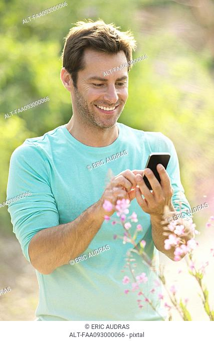 Mature man using cell phone while enjoying the great outdoors
