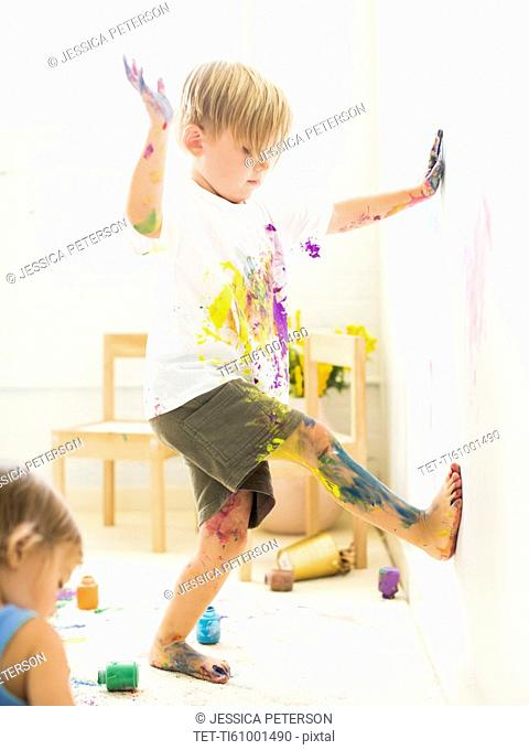 Boy (2-3) painting on wall with hands and legs