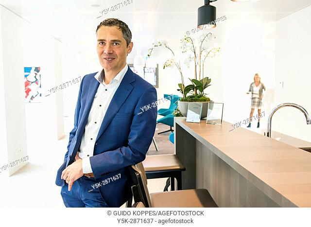Geldrop, Netherlands. Editorial portrait of a male, caucasian banker at his bank-office reception desk