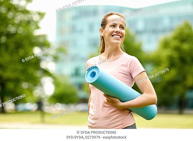 happy smiling woman with exercise mat at city park