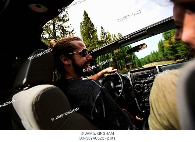 Over shoulder view of young couple driving in jeep