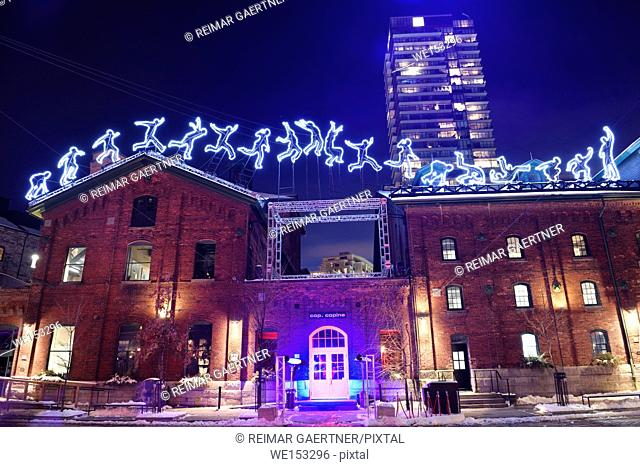 Light sculpture at Toronto Light Festival of running jumping tumbling man on roof of historic brick building at Distillery District