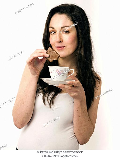 A young woman with brown hair and eyes dunking a chocolate biscuit into a cup of tea