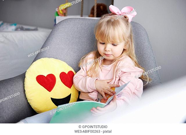 Portrait of blond little girl sitting in arm chair looking at picture book