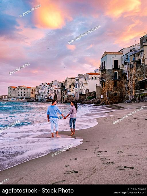 couple on vacation Sicily visiting the old town of Cefalu, sunset at the beach of Cefalu Sicily, old town of Cefalu Sicilia panoramic view at the colorful...