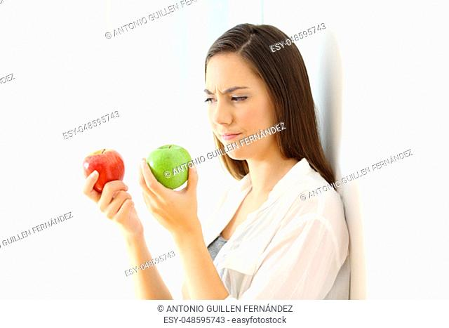 Doubtful woman deciding between red and green apples isolated on white at side