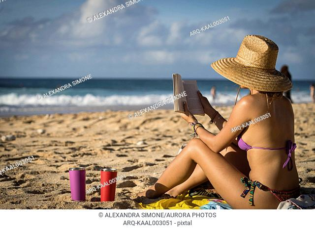 Woman in bikini and sun hat sitting and reading book on beach, Oahu, Hawaii Islands, USA