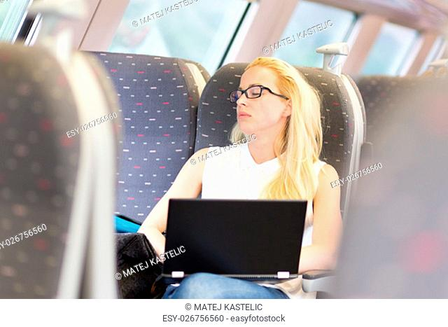 Businesswoman naping sitted while traveling by train and working on laptop. Tiresome business travel