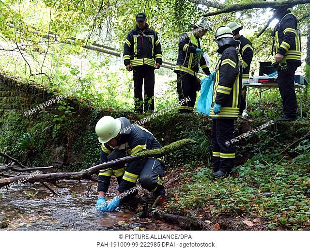 09 October 2019, Rhineland-Palatinate, Zemmer-Rodt: Members of the Rodt Volunteer Fire Brigade take water samples from the Winter Creek