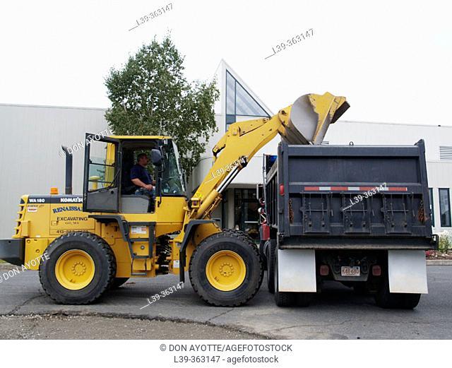 Dump truck and front end loader removing asphalt in Turners Falls, Massachusetts. USA