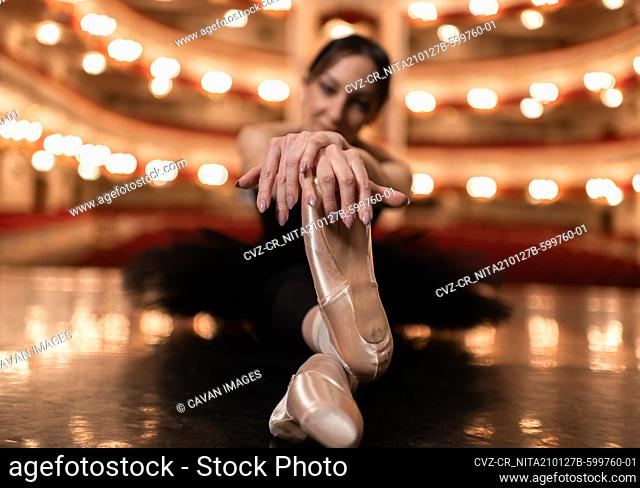 Ballerina stretching on stage before performance