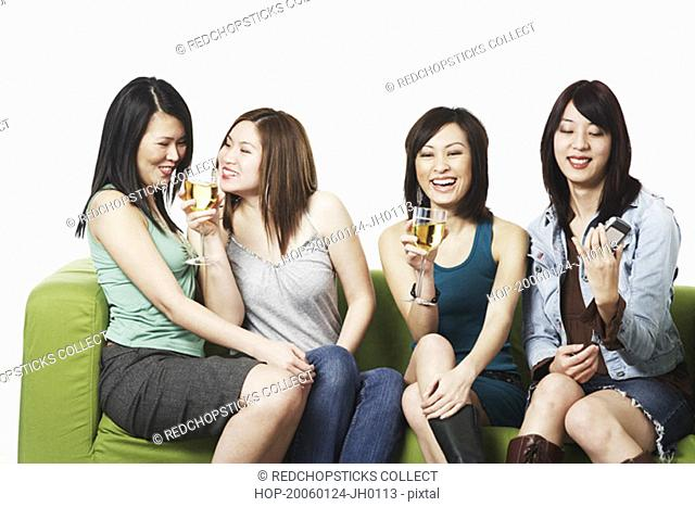 Close-up of four young women sitting on a couch smiling