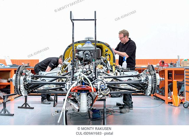 Engineers constructing racing car in racing car factory