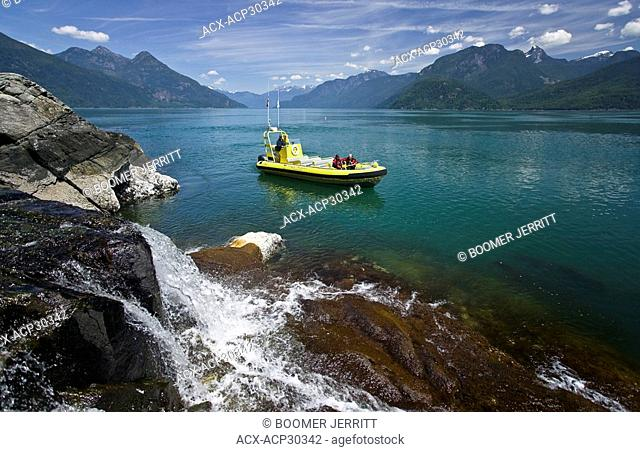 The waters of Bute Inlet turn an emerald green during the spring runoff, where fresh water form the surrounding mountains empties into the salt water