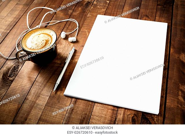 Blank branding template on vintage wooden table background. Blank letterhead, coffee cup, headphones and pen. Photo of blank stationery
