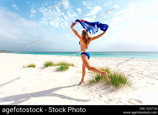 A woman leaps into the air holding the Australian flag while running along a white sandy idyllic beach in Australia. Australian travel, vacation, tourism
