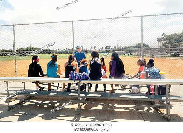 Male teacher instructing schoolgirl soccer players on school sports field bench