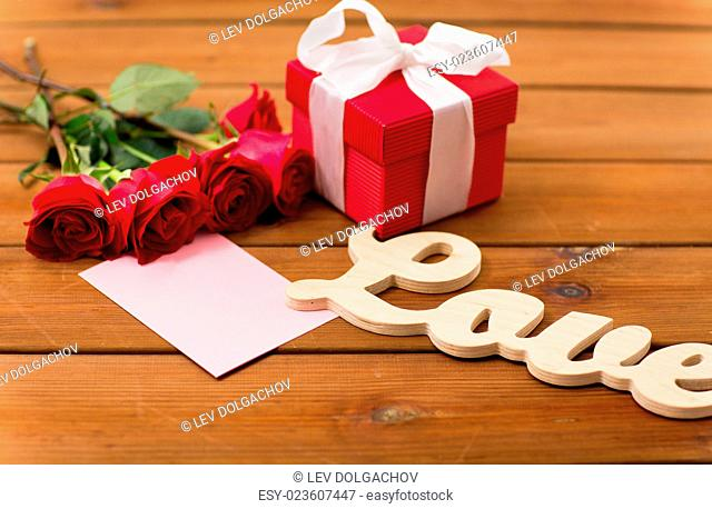 love, romance, valentines day and holidays concept - close up of gift box, red roses and greeting card with heart on wood