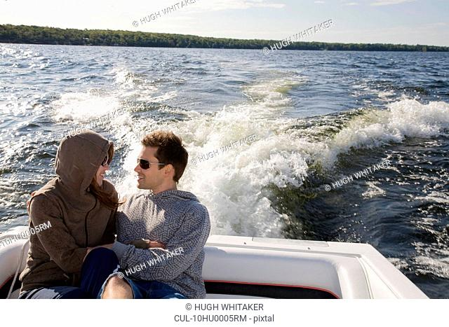 Couple sitting in speedboat on lake