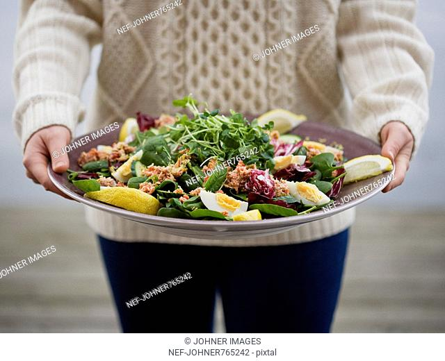 Woman with a plate of salad with crab, Sweden