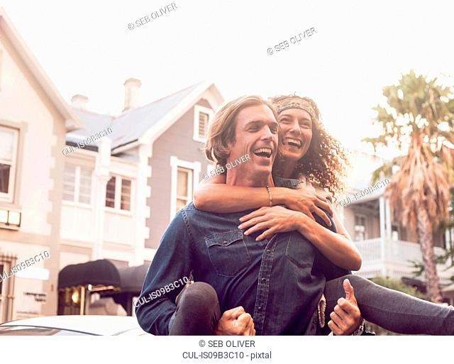 Man giving girlfriend piggyback on street, Cape Town, South Africa