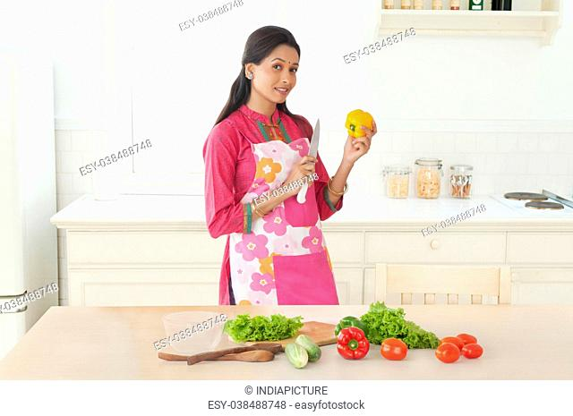 Woman holding capsicum and knife