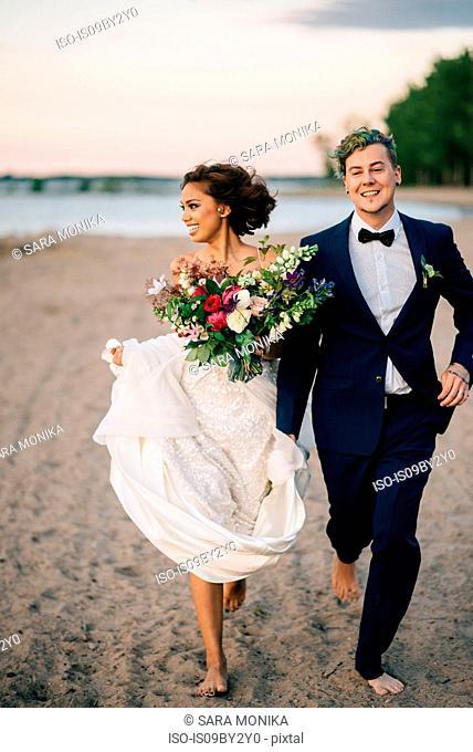 Bride and groom running barefoot on lakeside, Lake Ontario, Toronto, Canada