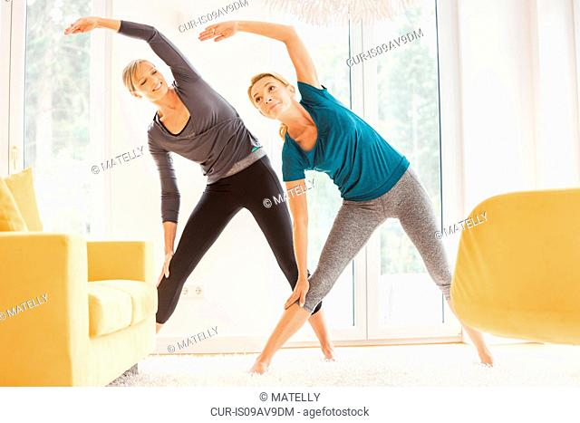 Two mature women bending over sideways whilst exercising in living room