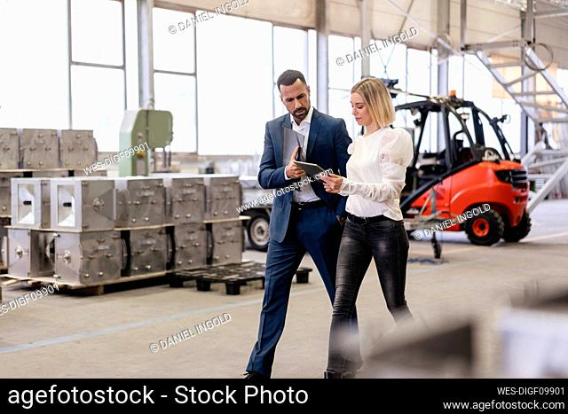 Businessman and young woman with tablet walking and talking in a factory