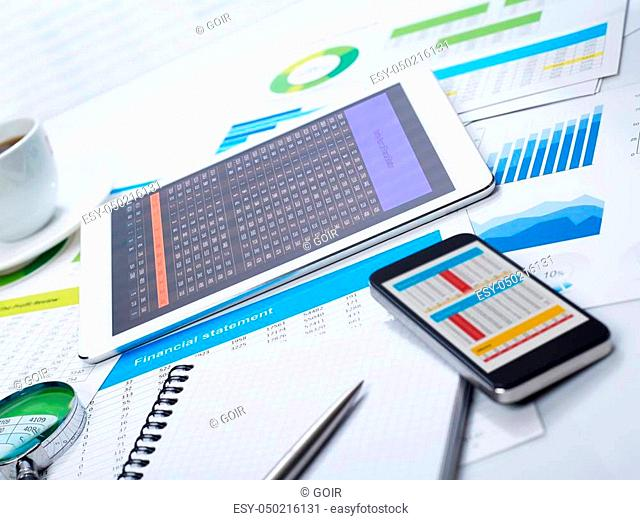 Tablet on desk and financial papers