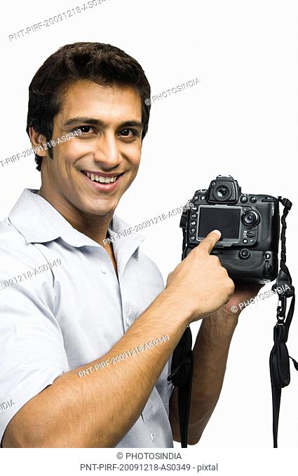 Photographer showing a digital camera and smiling