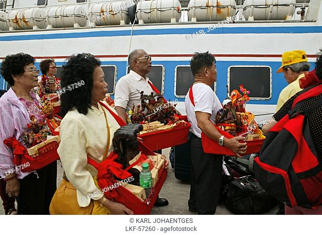 pilgrims at ferry, Buddha statues from house altars brought to Guanyin, Goddess of Mercy, Buddhist Island of Putuo Shan near Shanghai, Zhejiang Province