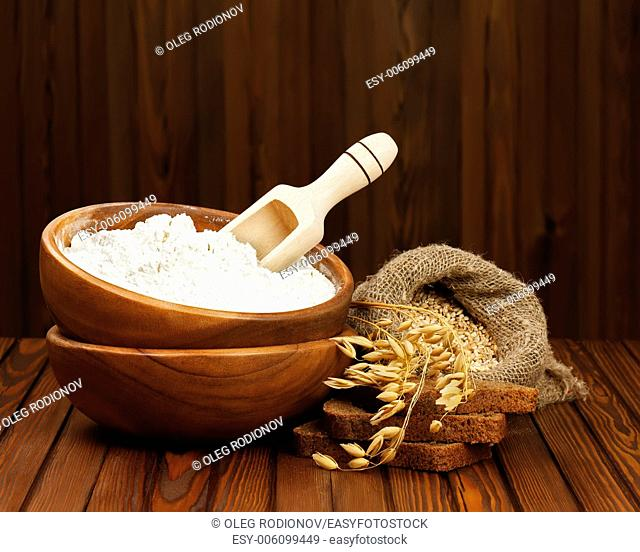 Flour in wooden bowl and wheat in burlap bag. Closeup
