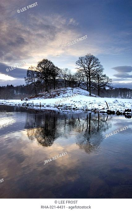 Winter view of River Brathay at dawn, under snow with reflections, near Elterwater Village, Ambleside, Lake District National Park, Cumbria, England