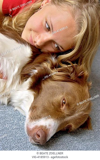 Teenage girls making out with her lying on the carpet dog , - Schenefeld, Schleswig-Holstein, Germany, 18/06/2006