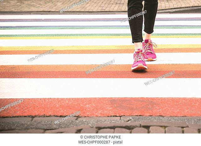 Woman crossing multi coloured zebra crossing, partial view