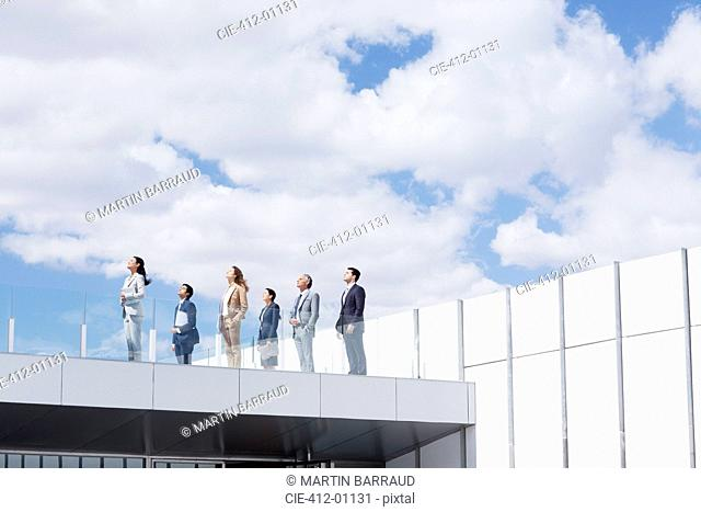 Business people on rooftop balcony looking up at sky