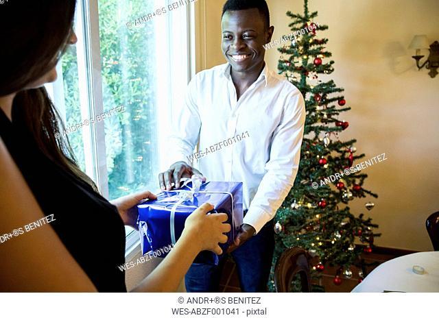 Man handing over Christmas present to woman