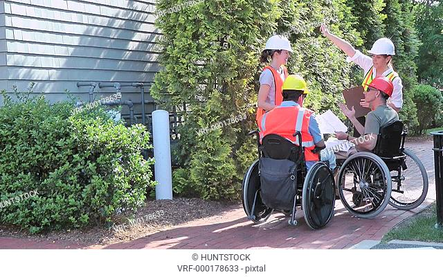 Construction engineers meeting, two in wheelchairs with spinal cord injuries