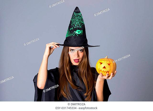 Beautiful young woman in black costume of witch with black hat holding a pumpkin and touching her hat on blue background in studio