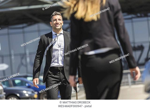 Smiling businessman with luggage at car park looking at woman