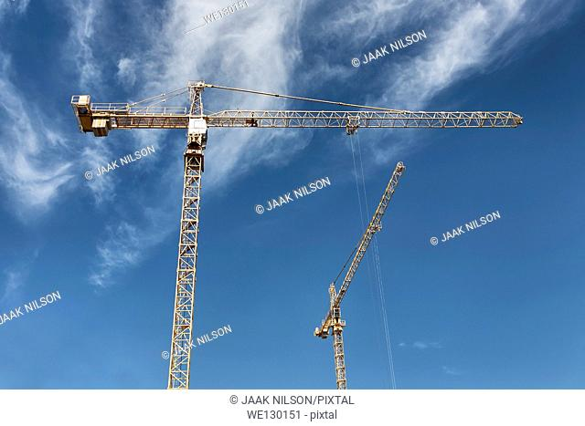 Two cranes against blue sky. Construction work