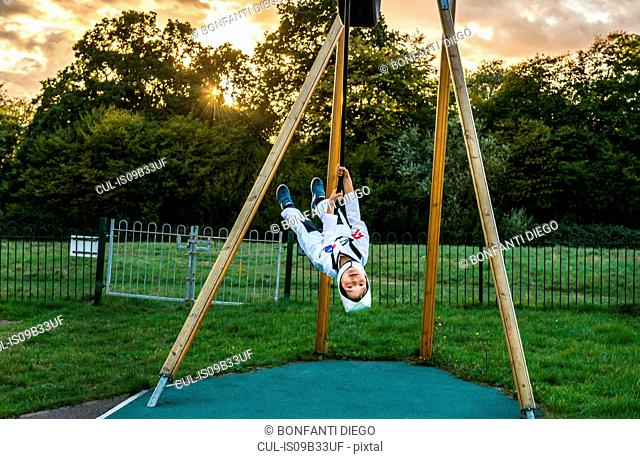Portrait of boy in astronaut costume riding upside down on playground zip wire