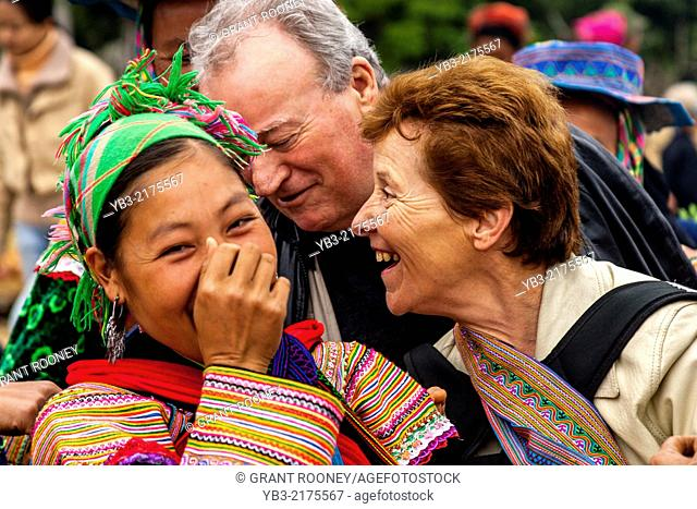 Flower Hmong Woman and Tourists Share A Joke At The Sunday Market In Bac Ha, Lao Cai Province, Vietnam