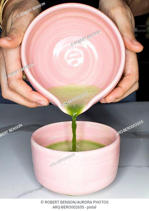 A person prepares green tea matcha in colorful pink bowl