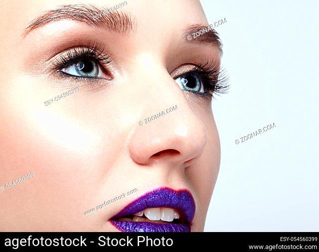 Closeup macro shot of human woman face. Female with natural eyes makeup and bright violet lips