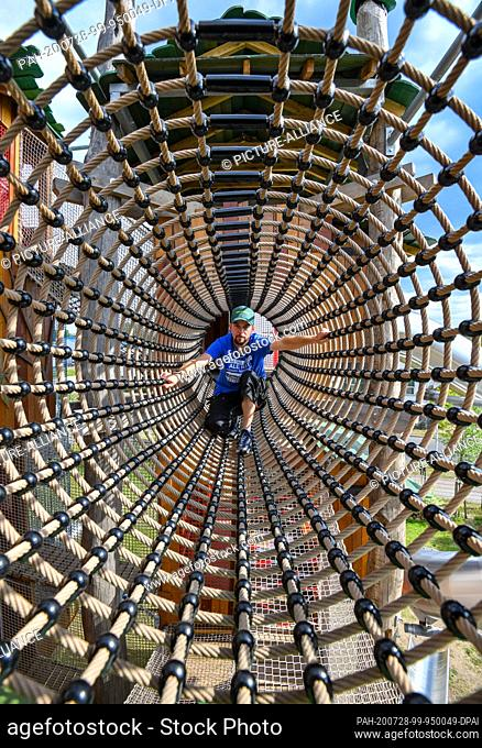 """28 July 2020, Brandenburg, Storkow: Stephan Rieger, employee in the """"""""Irrlandia"""""""" interactive park, checks a climbing tunnel in the labyrinth of heights before..."""